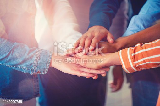 istock Group of workers holding hands in celebration. Collaboration concept. 1142090759