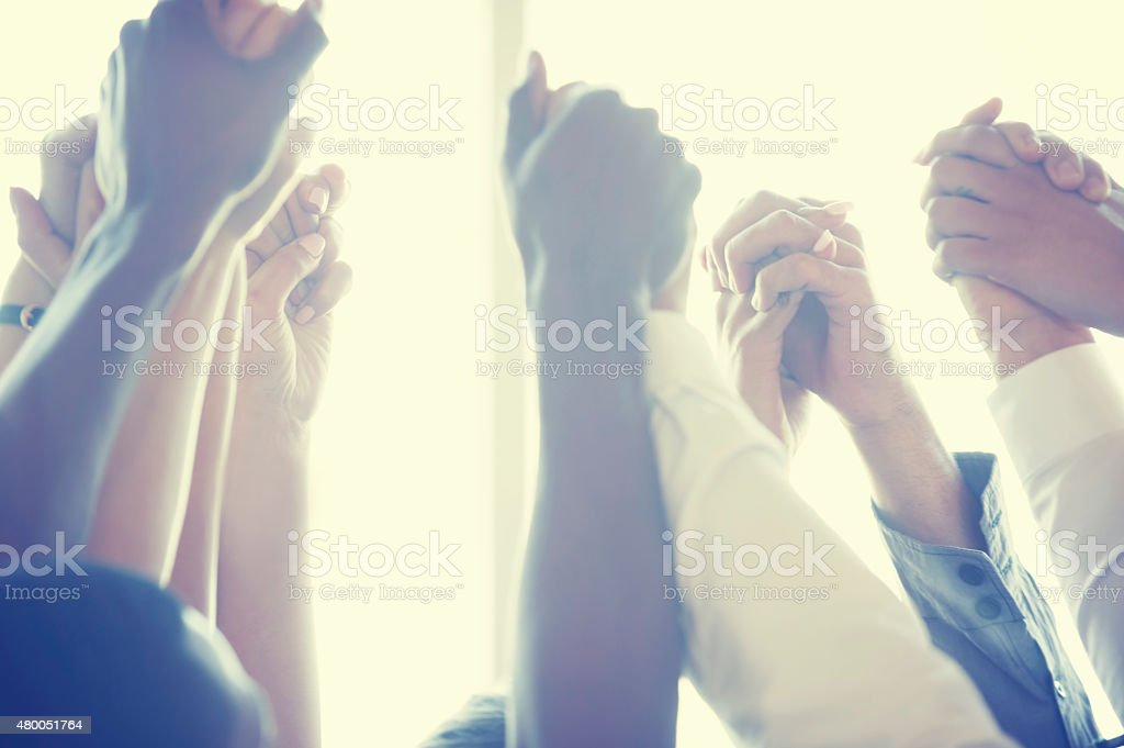 Group of workers holding hands in celebration. stock photo