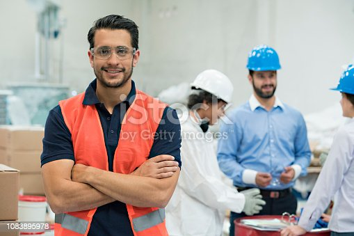 Group of engineers and workers, discussing the working model of the day, all very focused, while there is one standing in front of the camera smiling