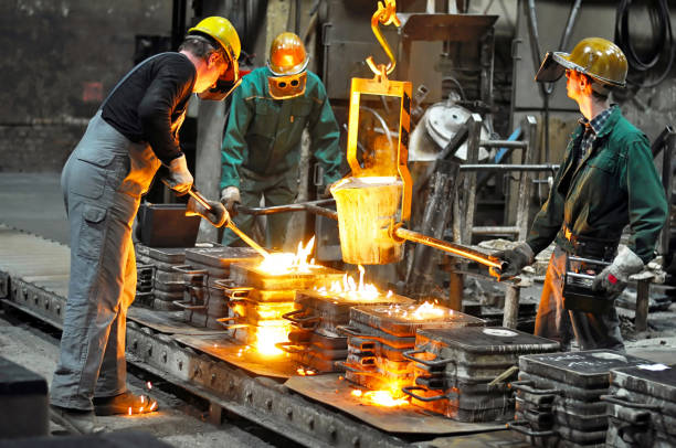 Group of workers in a foundry at the melting furnace - production of steel castings in an industrial company stock photo