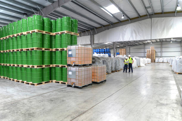 group of workers in the logistics industry work in a warehouse with chemicals group of workers in the logistics industry work in a warehouse with chemicals chemical plant stock pictures, royalty-free photos & images