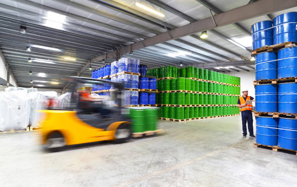 group of workers in the logistics industry work in a warehouse with chemicals - lifting truck - chemical stock photos and pictures