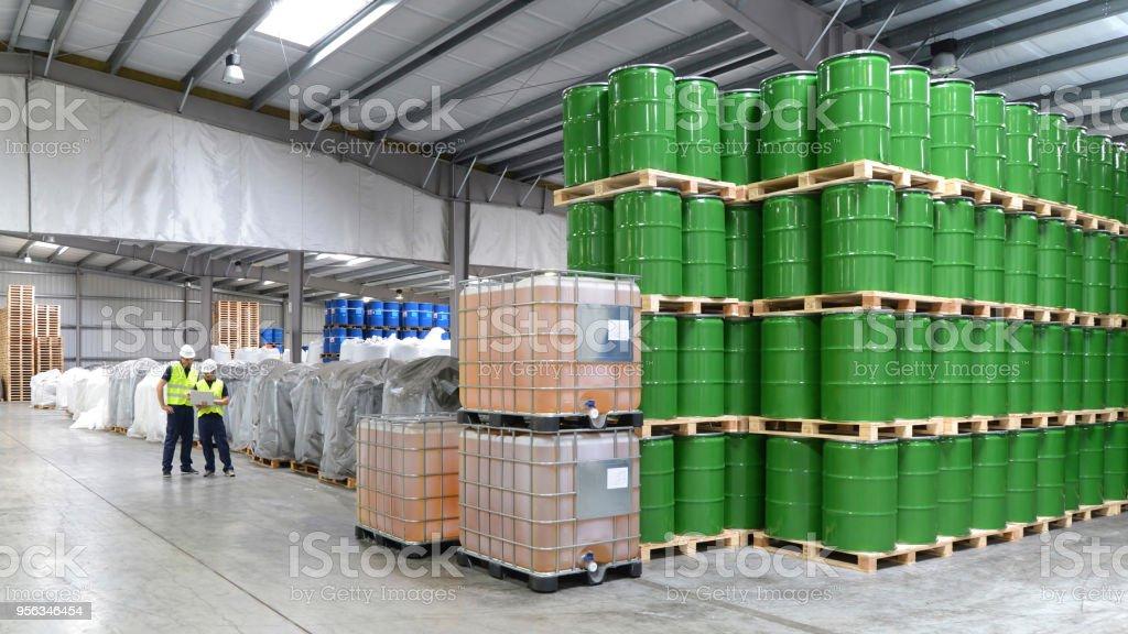 grupo de trabalhadores na indústria de logística trabalha em um armazém com produtos químicos - foto de acervo