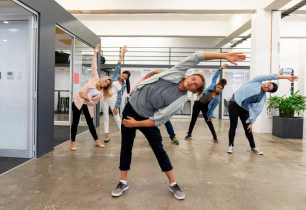 gruppe der arbeitnehmer auf eine aktive pause bei einem kreativ-büro - yoga fürs büro stock-fotos und bilder