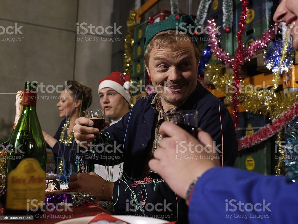 Group of workers sitting at christmas table in warehouse holding wine glasses royalty-free stock photo
