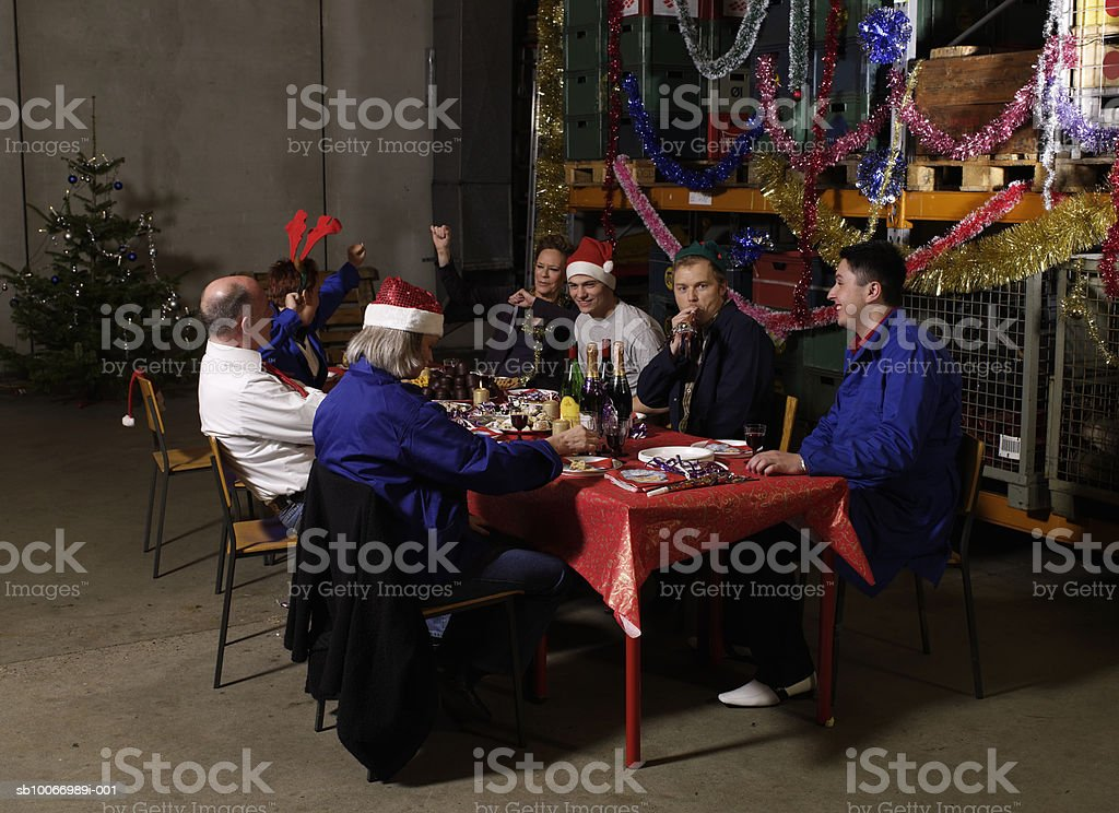 Group of workers sitting at christmas table in warehouse royalty-free stock photo