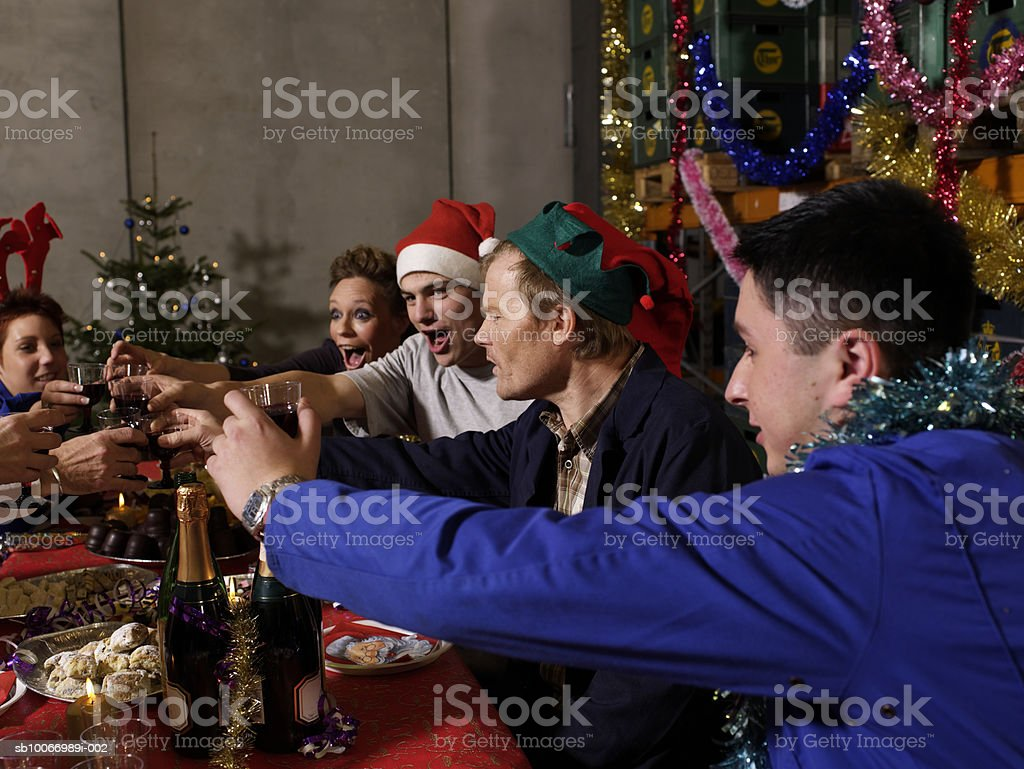 Group of workers sitting at christmas table in warehouse toasting with wine glasses royalty-free stock photo