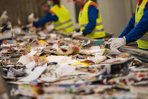 gruppe von arbeitnehmern sortierung zeitung beim recycling-plant - papier recycling stock-fotos und bilder