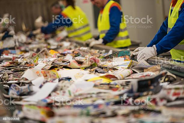 Workers sorting papers on factory assembly line for recycling at recycling plant.