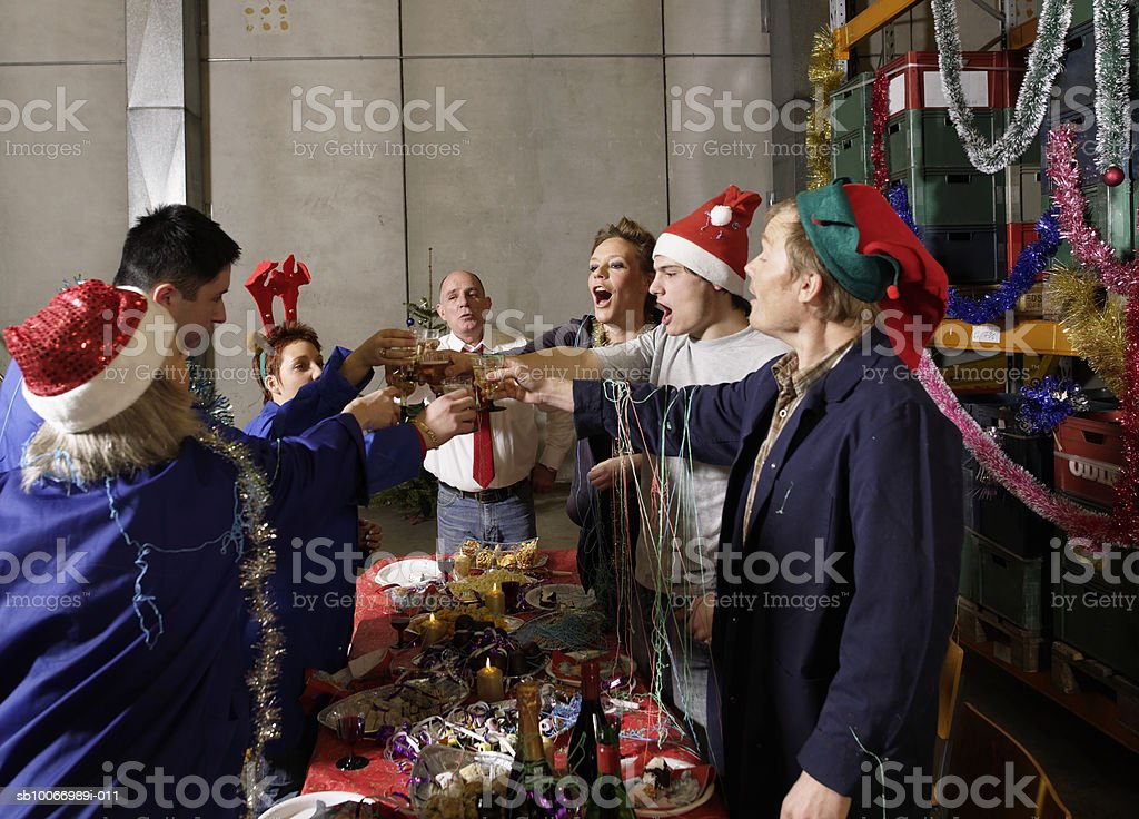 Group of workers standing, toasting with champagne at christmas table in warehouse royalty-free stock photo