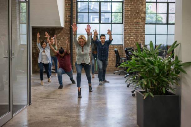 gruppe der arbeitnehmer, die eine pause von der arbeit - yoga fürs büro stock-fotos und bilder