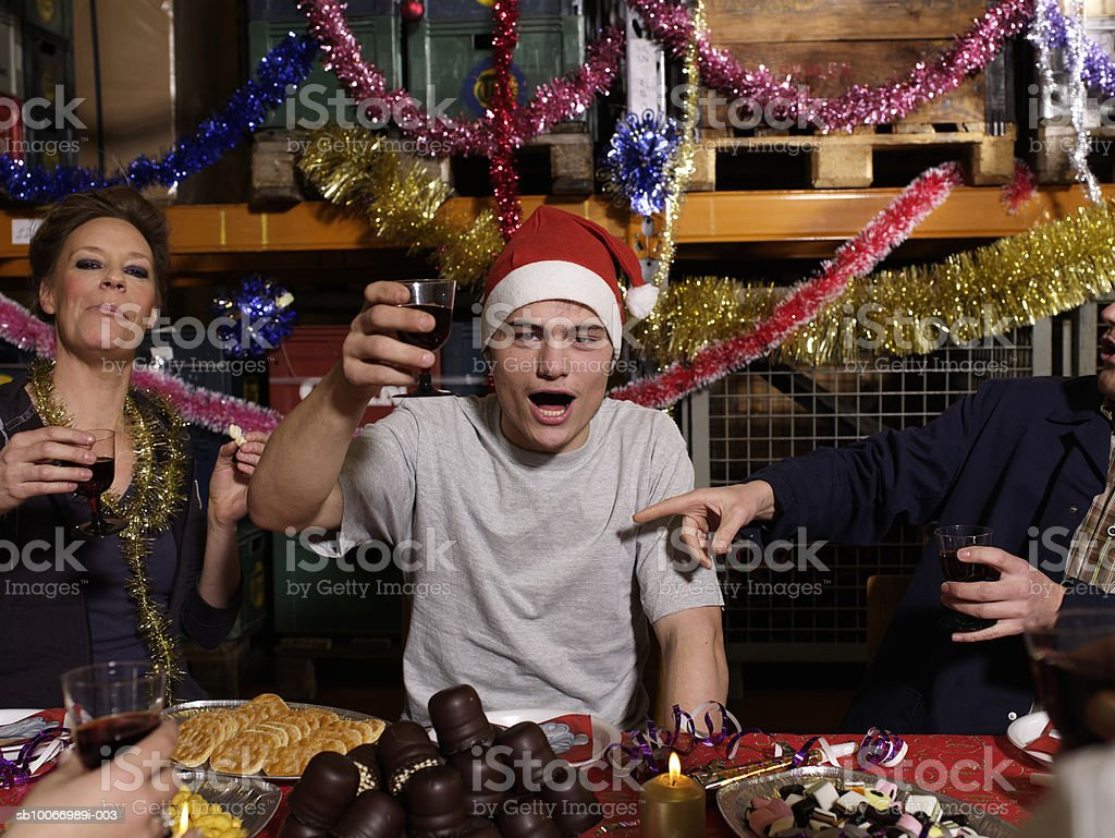 Group of workers toasting with wine glasses at Christmas table in warehouse, portrait royalty free stockfoto
