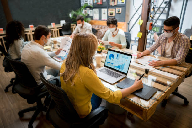 Group of workers wearing facemasks while working at the office stock photo