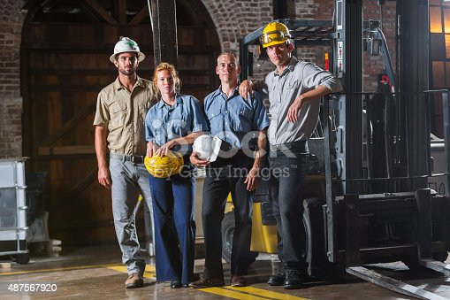 A group of four workers with hardhats, including a young woman, standing side by side, looking at the camera.  They are in a warehouse next to a forklift.