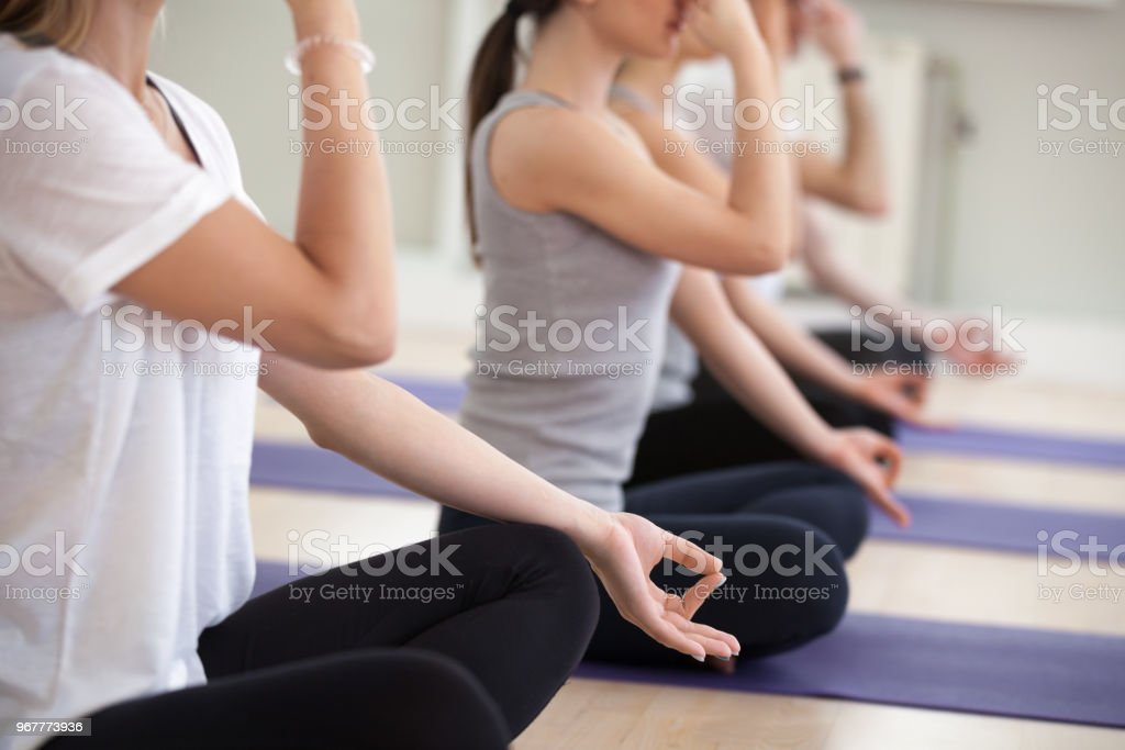 Group of yogi people practicing Alternate Nostril Breathing, close up stock photo