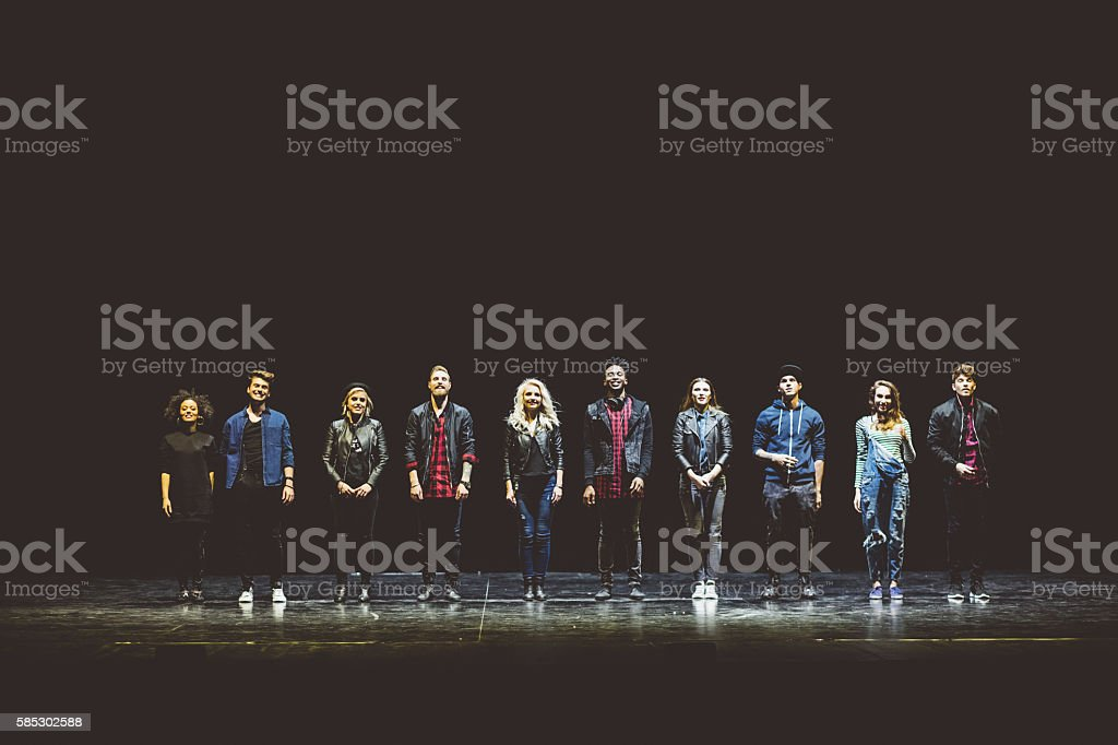 Group of young actors on the stage Group of young performers on the stage standing in the line. Dark tones. 20-29 Years Stock Photo
