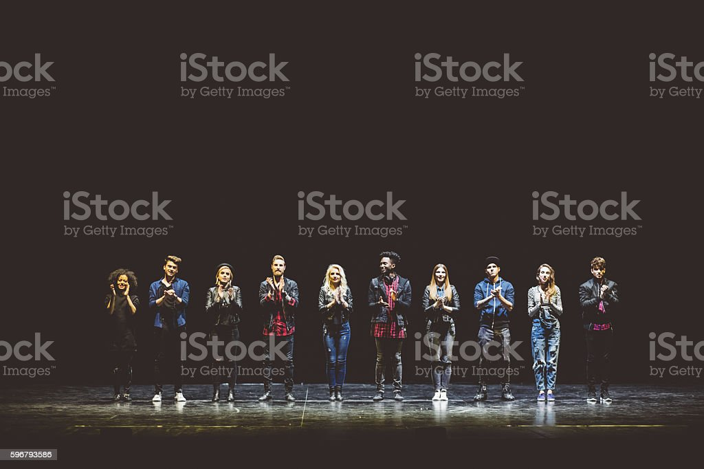 Group of young actors on the stage Group of young performers on the stage standing in the line, clapping hands. Dark tones. 20-29 Years Stock Photo