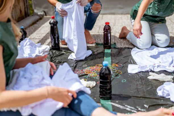 Gruppe junger erwachsener Menschen, die Krawattenfärberei-Kleidung im Freien auf dem Dach herstellen – Foto