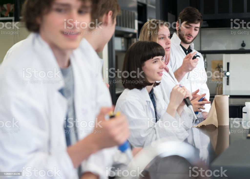Group of young adult students in college science laboratory. stock photo