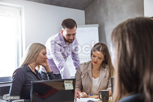 istock Group of young adult successfull people working together in office 854996400