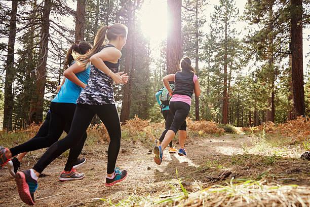 grupo de adulto joven mujer corriendo en el bosque, espalda - trail running fotografías e imágenes de stock