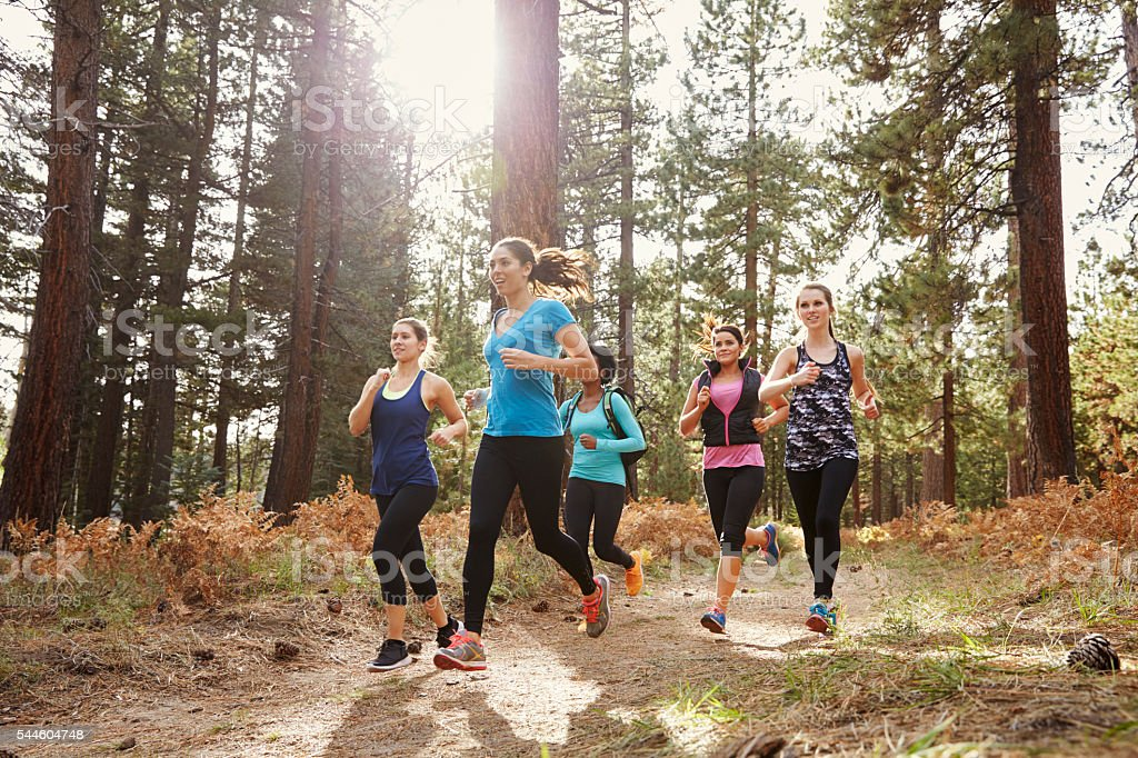 Group of young adult women running in a forest, close stock photo