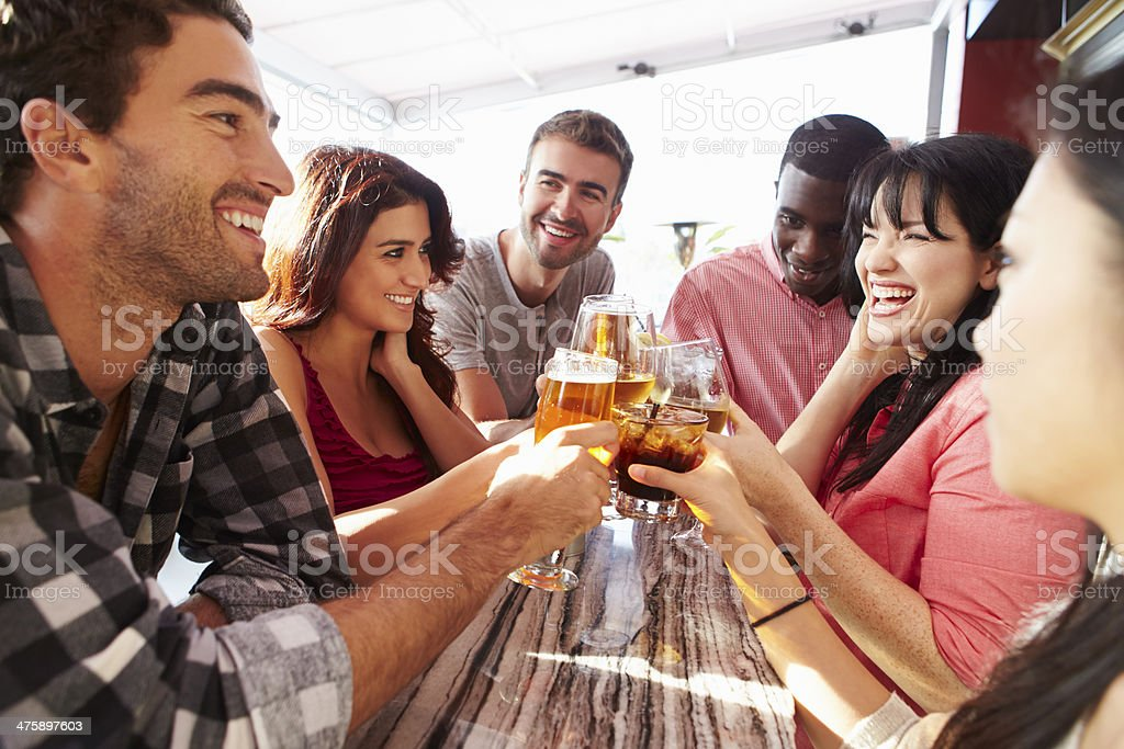 Group of young adults drinking at a rooftop bar stock photo