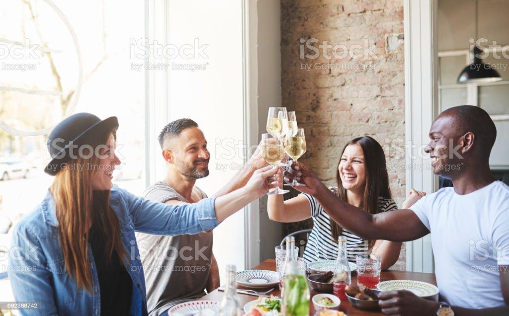 Groupe de jeunes adultes boire ensemble à table photo libre de droits