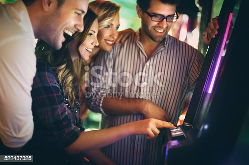 Group of young adults in late 20's playing slot poker and fruits and wining.Wearing casual clothes and having fun on weekend night. There are many slot machines out of focus in background.
