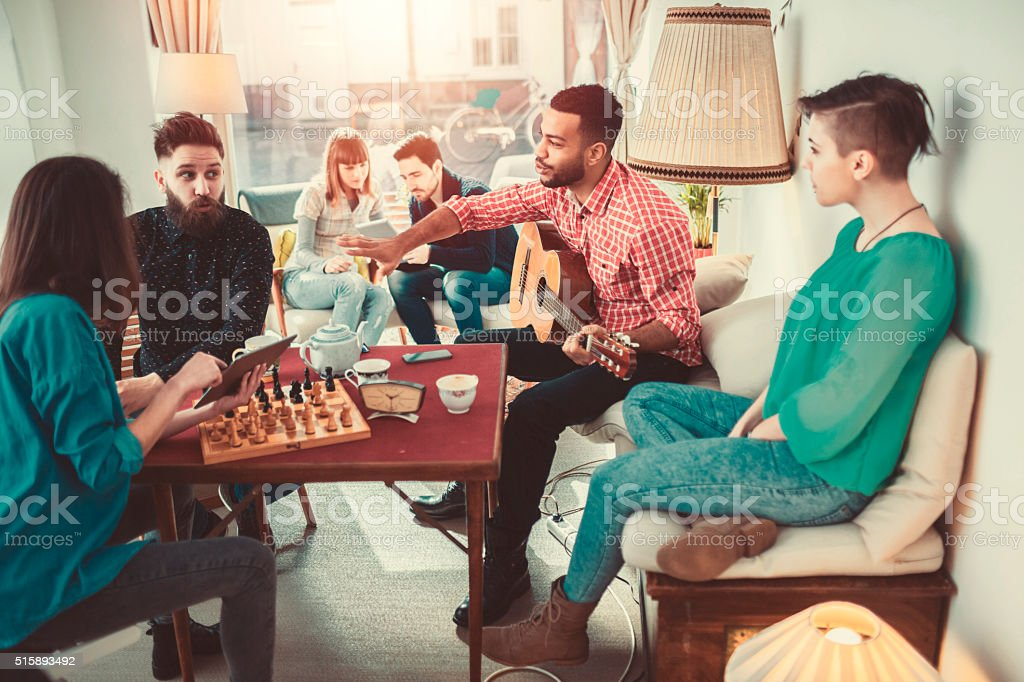 Group of young adults having fun in coffee shop stock photo