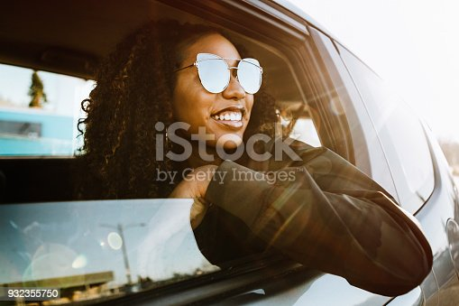 A smiling group of Generation Z young adults enjoy a road trip on a sunny day.  Mixed ethnic group.  Horizontal image with copy space.