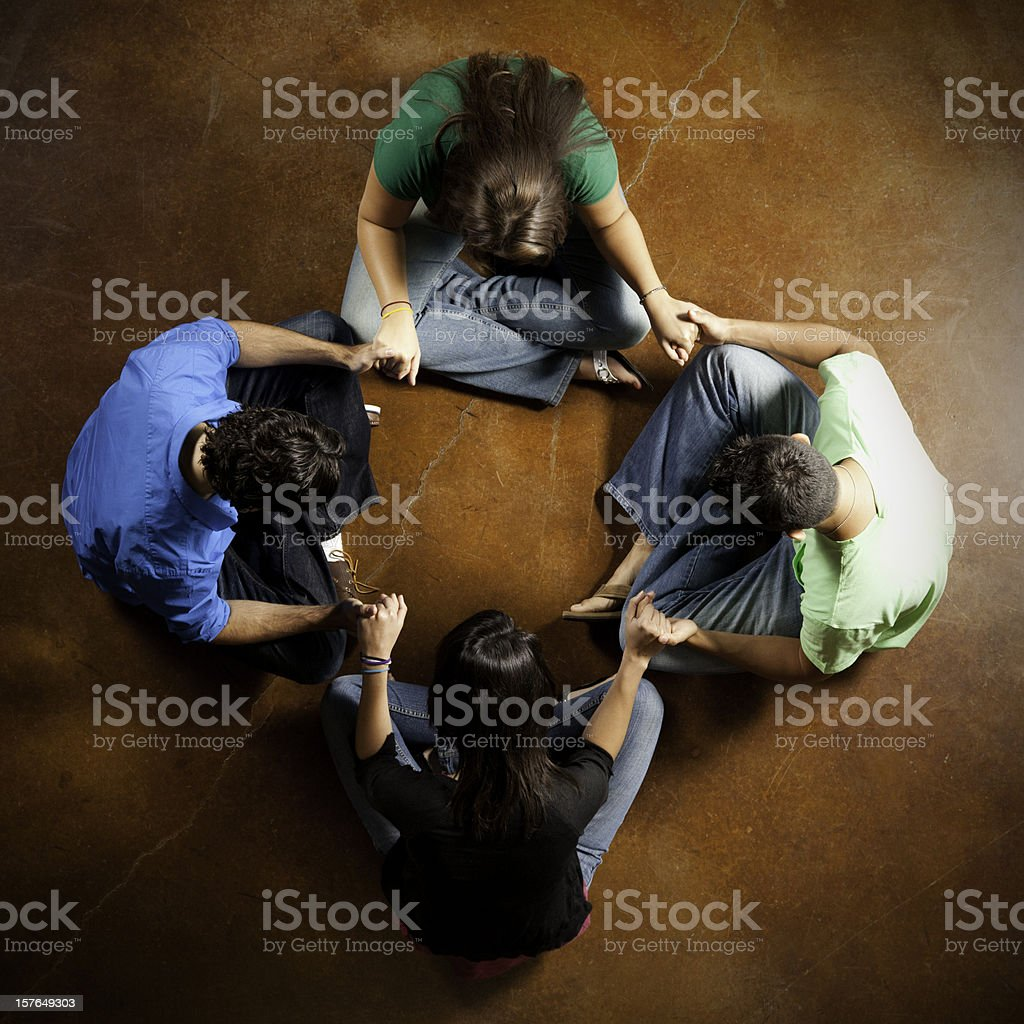 Group of Young Adults Holding Hands and Praying Together royalty-free stock photo