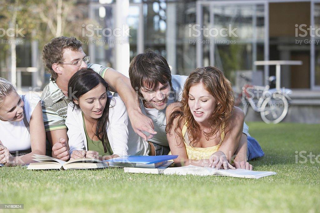 Grupo de jovens adultos pôr na grama ao ar livre com Livros foto de stock royalty-free