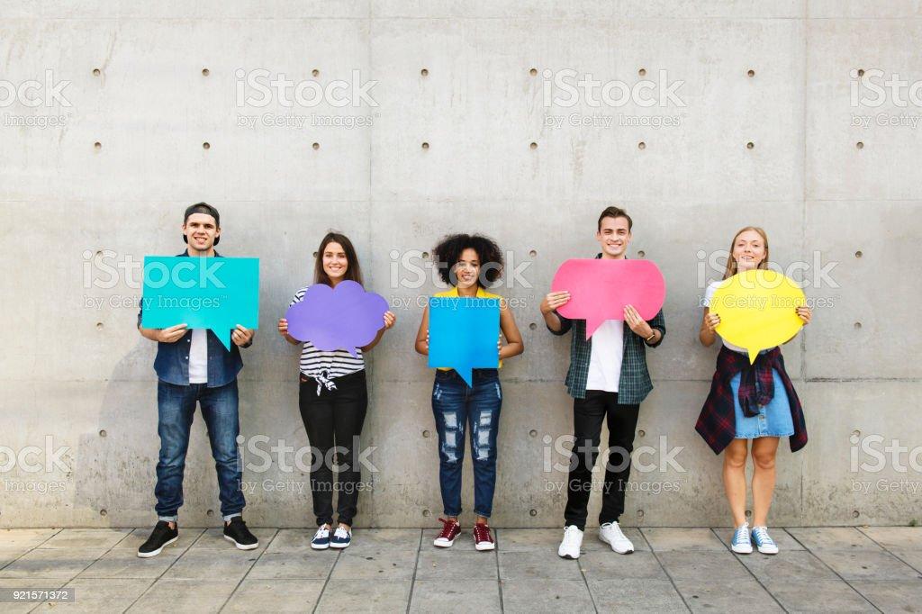 Grupo de jovens adultos no exterior segurando cartaz vazio balões de pensamento de cópia-espaço - foto de acervo