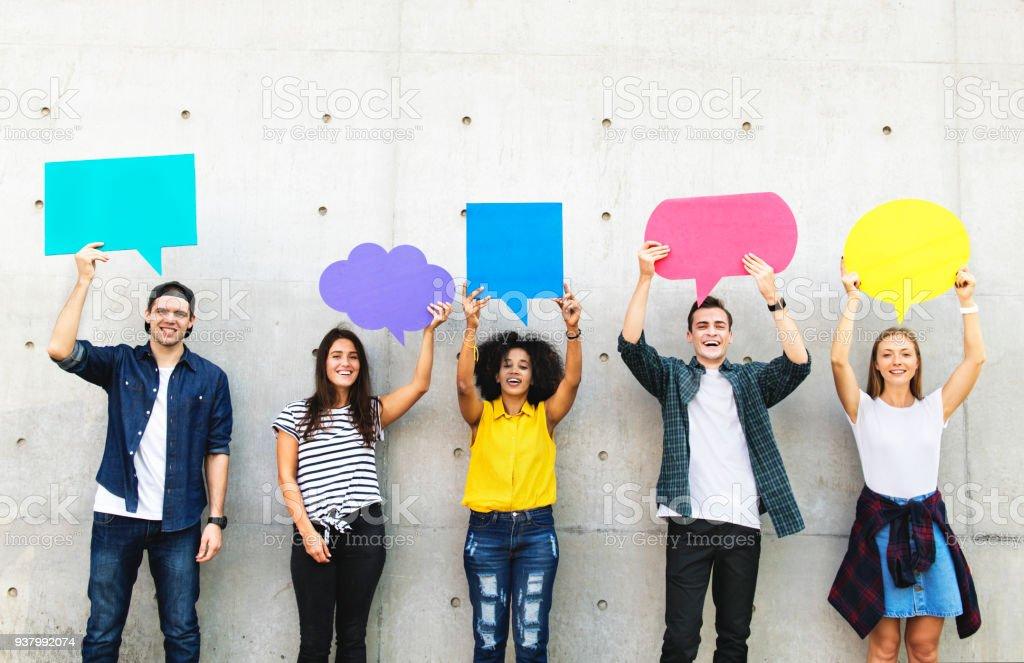 Grupo de jovens adultos ao ar livre, segurando balões de pensamento vazio cartaz copyspace - foto de acervo