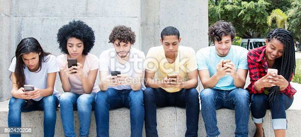 istock Group of young adults playing online game with phone 892420208