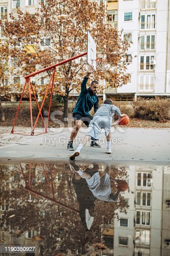 Group of young adults plays basketball