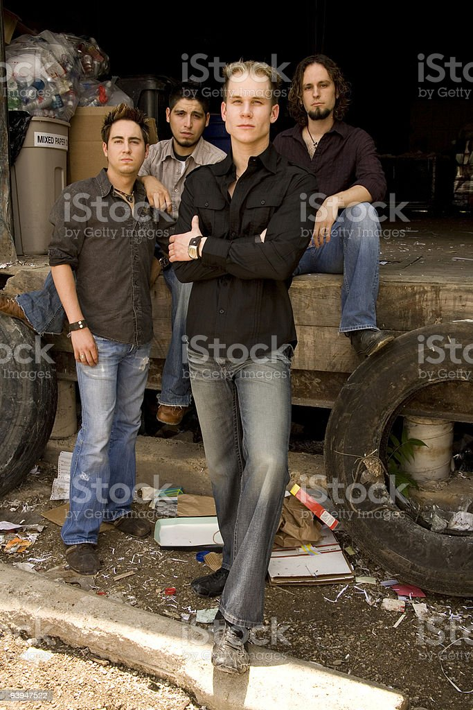 Group of young adults posed by a trash dump royalty-free stock photo
