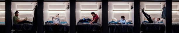 groep van jonge volwassenen ontspannen in een capsule hotel - claustrofobie stockfoto's en -beelden