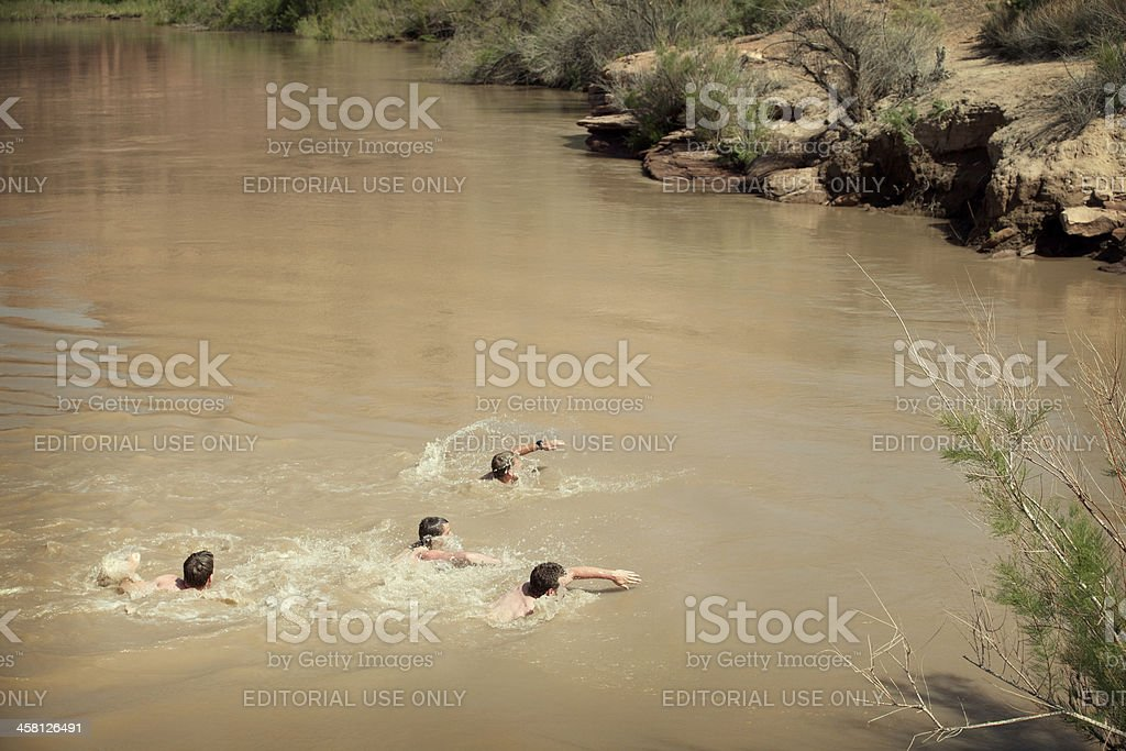 Group of young adults swimming in a river. stock photo