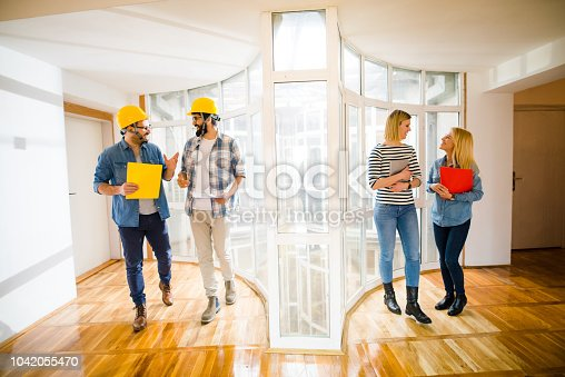 521012560 istock photo Group of young architects walking through empty bright room and discussing about next steps. 1042055470