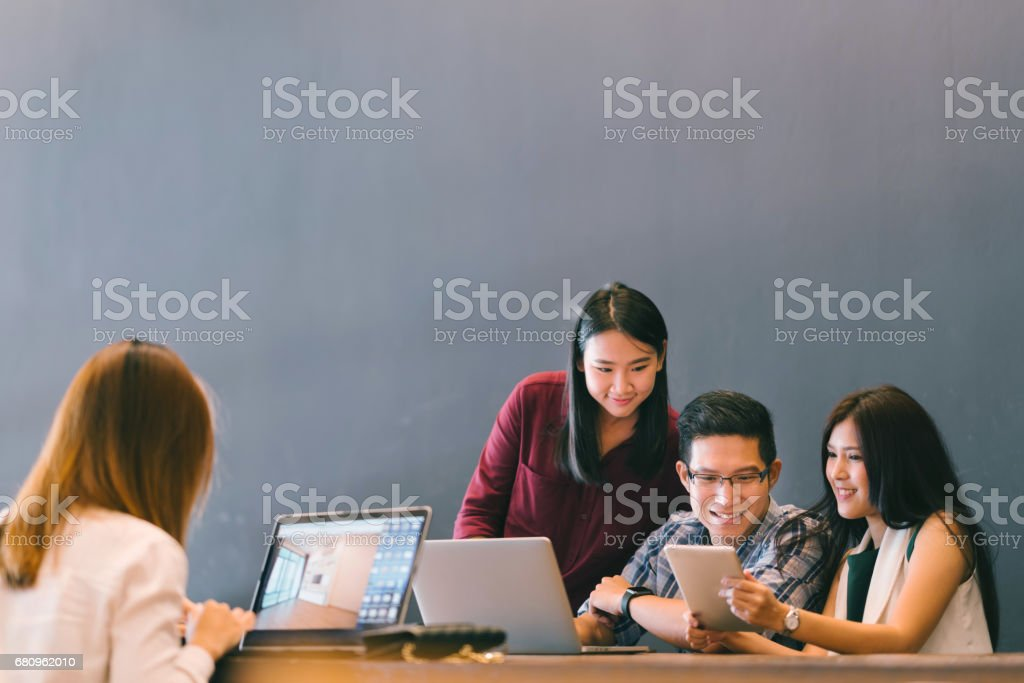 Group of young Asian business colleagues in team casual discussion, startup project business meeting or happy teamwork brainstorm concept, with copy space, depth of field effect stock photo