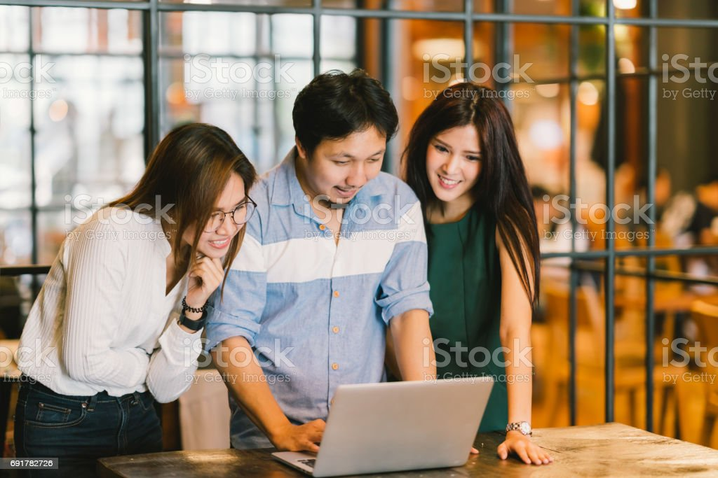 Group of young Asian business colleagues in team casual discussion, startup project business meeting or happy teamwork brainstorm concept, with copy space, depth of field effect, focus on the man stock photo