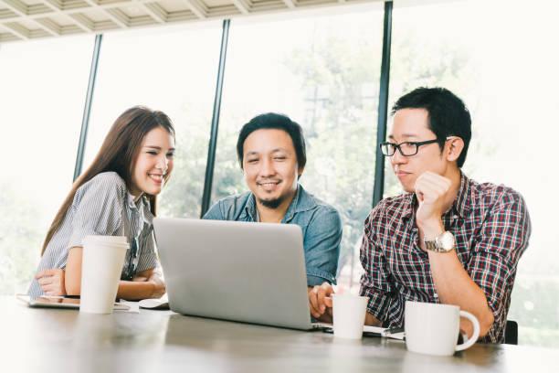 チームカジュアルディスカッション、スタートアッププロジェクトミーティング、または幸せなチームワークブレーンストーミングコンセプトでラップトップを使用するアジアの若いビジネ� - 大学生 パソコン 日本 ストックフォトと画像