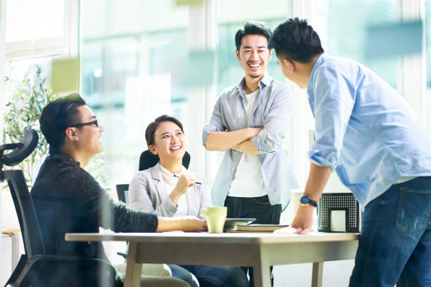 group of young asian business executives talking in office stock photo