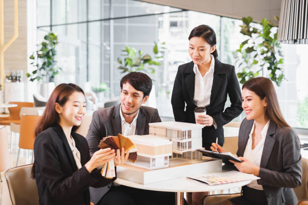 Group of young asian business people meeting in office for house real estate residence project stock photo