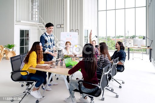 istock Group of young asian creative team talking, smile and laugh brainstorming, sharing or training on meeting or workshop at office. Happy asian workplace sitting attentive together in rear view concept. 1133946139
