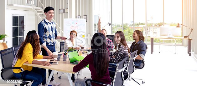 istock Group of young asian creative team talking, smile and laugh brainstorming, sharing or training on meeting or workshop at office. Happy asian workplace sitting attentive together in rear view concept. 1190093290