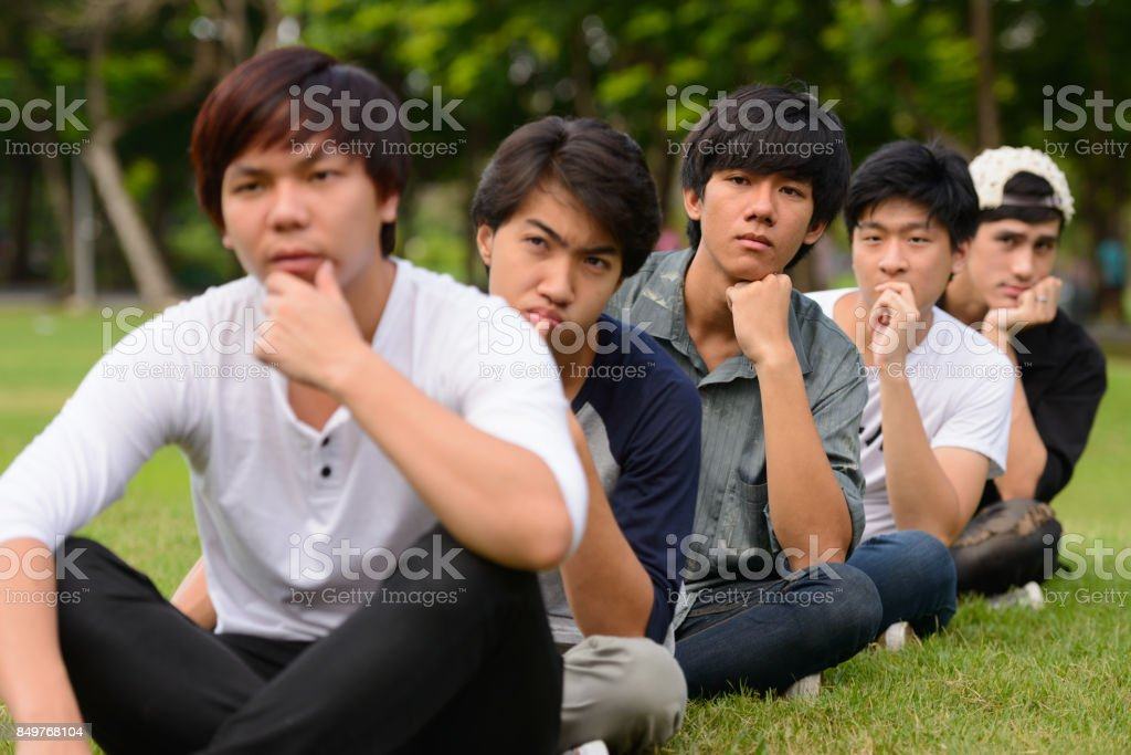 Group of young Asian friends hanging out and relaxing together at the park stock photo