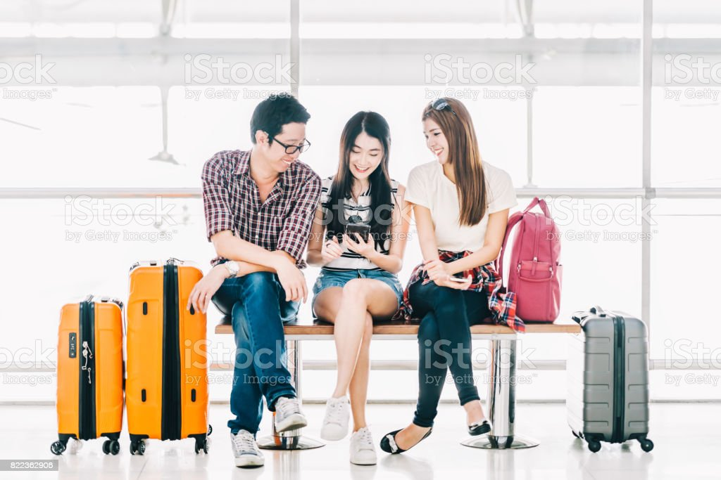 Group of young Asian travelers using smartphone checking flight or online check-in at airport together, with luggage. Travel abroad, summer holiday trip, or mobile phone application technology concept stock photo